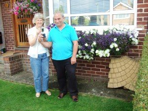 Couple holding silver cup, standing in front of prize windowbox