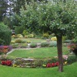 Terraced garden with lawns, flower beds shrubs and fruit tree