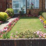 Colourful front garden with beds surrounding rectangular lawn