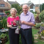 Couple standing in developed garden holding trophies