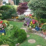 Colourful front garden with lawn edged around raised beds