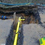 Yellow pipes and valves exposed below the surface of the road
